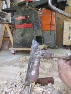 Using a bevel gauge to guide the auger's angle.